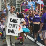 Care can't wait sign held by older gay man