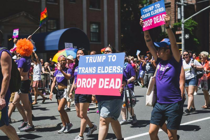 LGBT Pride marchers for SAGE hold signs in support of transgender elders