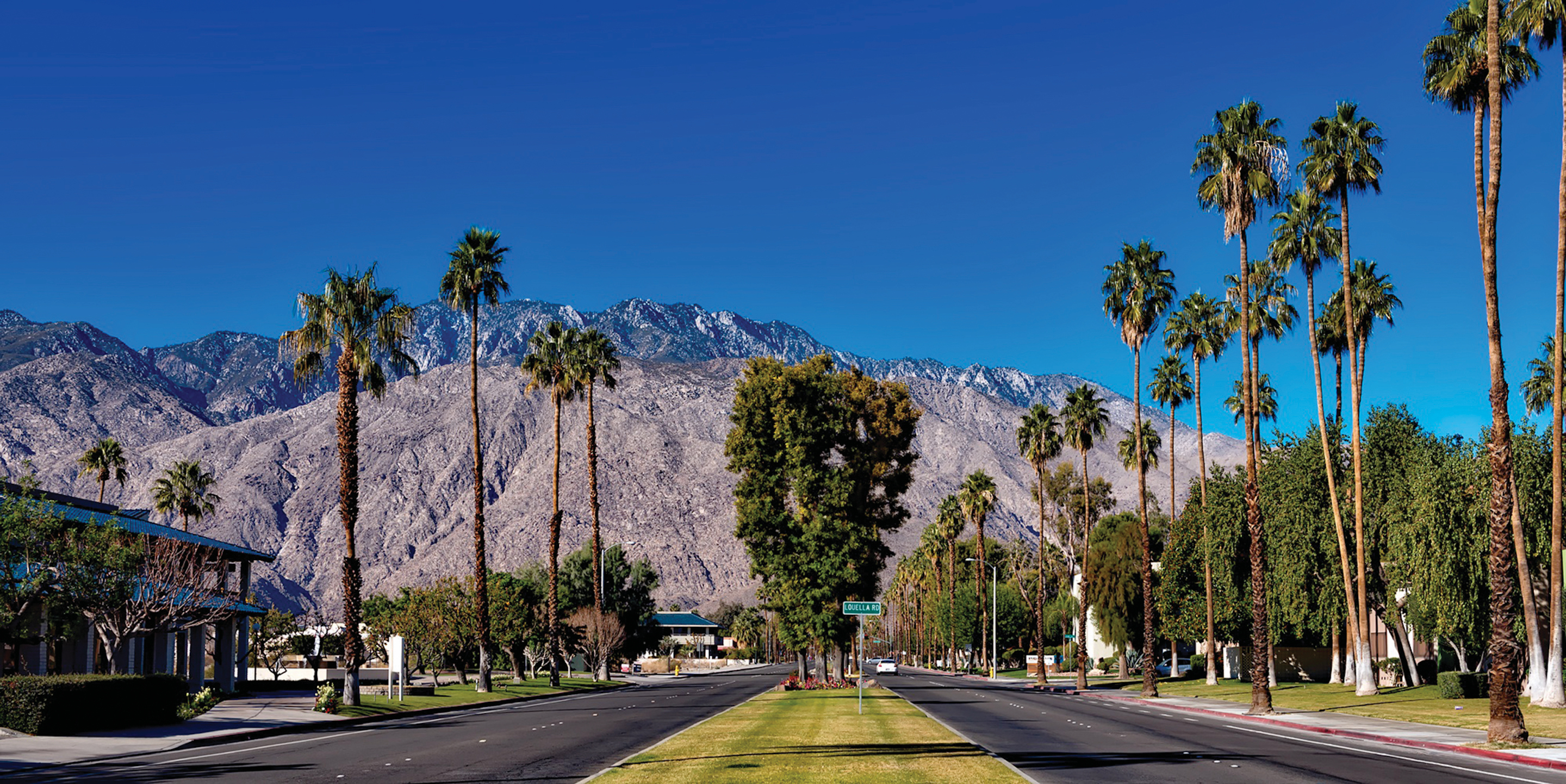 A two-way road showing palm trees and mountains