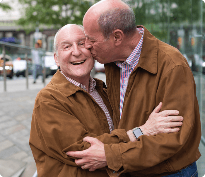 LGBT elder couple embracing in matching jackets