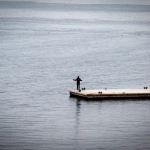 single-person-stands-on-dock