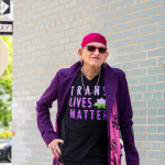 transgender-person-standing-outside-with-cane-and-trans-lives-matter-shirt
