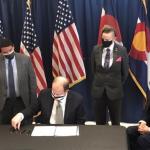 man-sitting-at-desk-signing-a-bill
